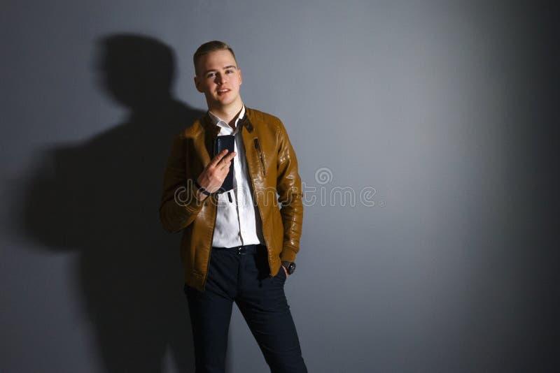 Красивый молодой человек в представлениях кожаной куртки стоковые изображения