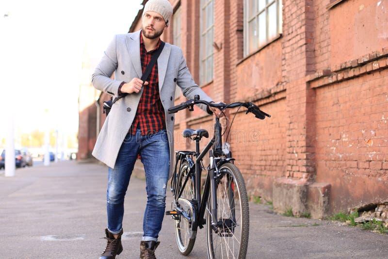 Красивый молодой человек в сером пальто и шляпе нажимая его велосипед вниз с улицы в городе стоковые фото