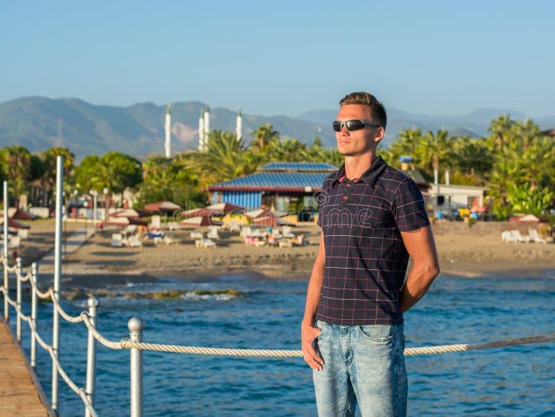 Красивый молодой человек в солнечных очках стоит на пристани на backgro стоковое изображение