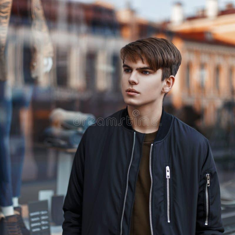 Красивый молодой человек в стильной черной куртке ходя по магазинам близко стоковое фото