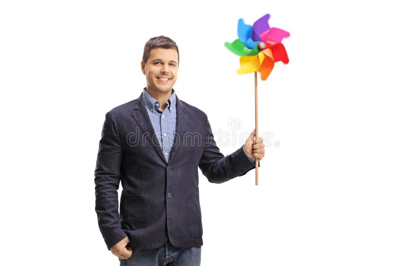 Красивый молодой человек держа красочный pinwheel и смотря камеру стоковое фото rf
