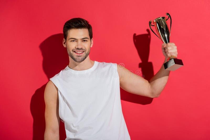 красивый молодой человек держа трофей и усмехаясь на камере стоковые изображения rf
