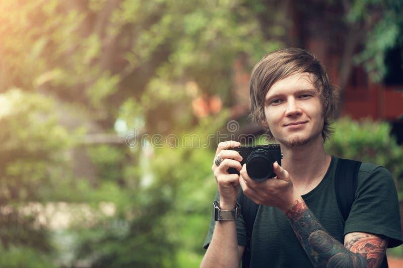 Красивый молодой человек держа цифровой фотокамера и усмехаться стоковое фото rf