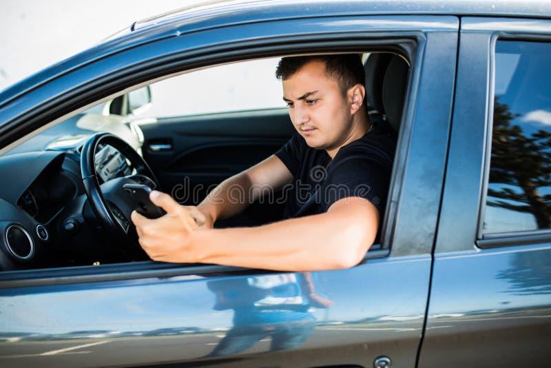 Красивый молодой человек используя мобильный телефон пока управляющ автомобилем стоковые изображения rf