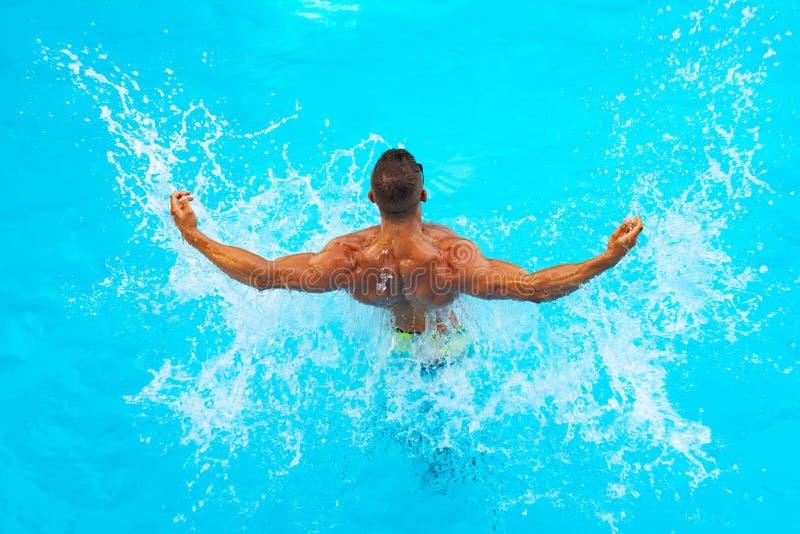 : Красивый молодой человек ослабляя на пляже Бассейн молодого человека стоковое изображение rf