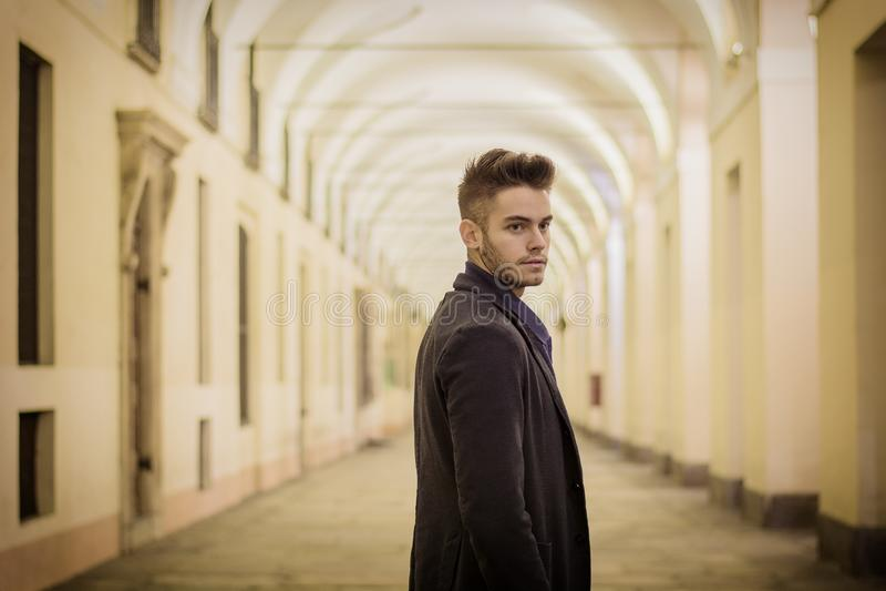 Красивый молодой человек под монастырями в итальянском городе на ноче стоковое фото