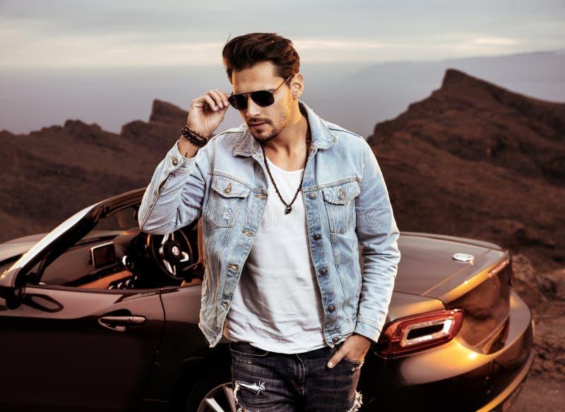 Красивый, молодой человек представляя рядом с его роскошным автомобилем с откидным верхом стоковые фотографии rf