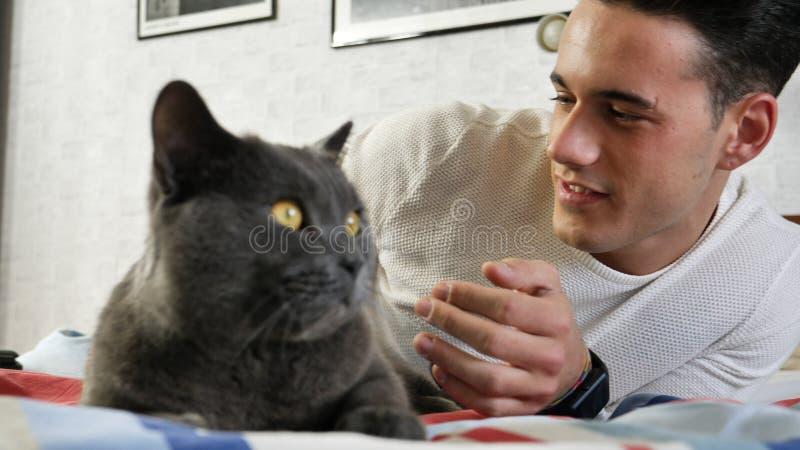 Красивый молодой человек прижимаясь его серый любимчик кота стоковая фотография