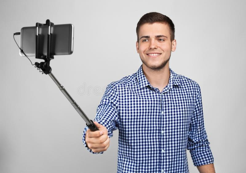 Красивый молодой человек принимая selfie на светлой предпосылке стоковая фотография rf