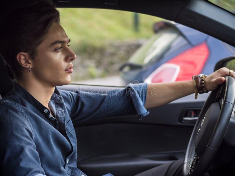 Красивый молодой человек сидя в его автомобиле, смотря прочь стоковые изображения rf