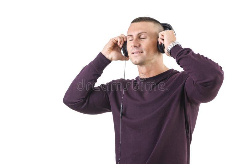 Красивый молодой человек слушая к нот на наушниках стоковые фото