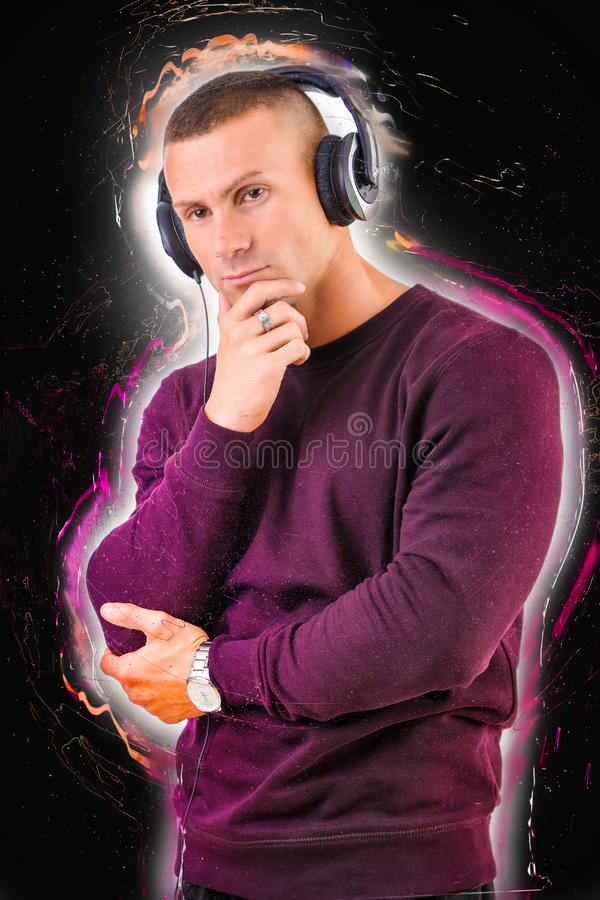 Красивый молодой человек слушая к нот на наушниках стоковые изображения
