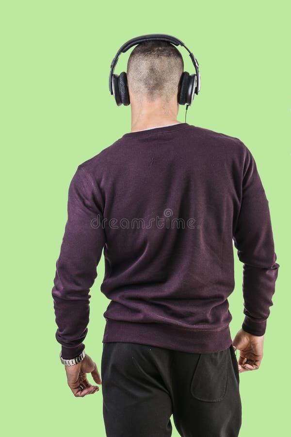 Красивый молодой человек слушая к нот на наушниках стоковая фотография rf