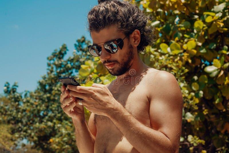 Красивый молодой человек с сотовым телефоном outdoors стоковое фото rf