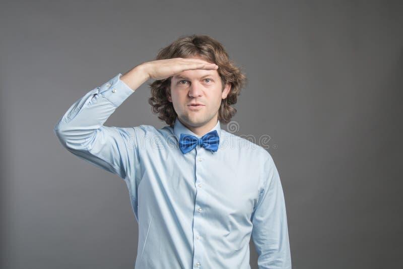 Красивый молодой человек с темным вьющиеся волосы нося голубую рубашку и бабочку кладя руку на его лоб и усмехаться, смотря далек стоковые изображения rf