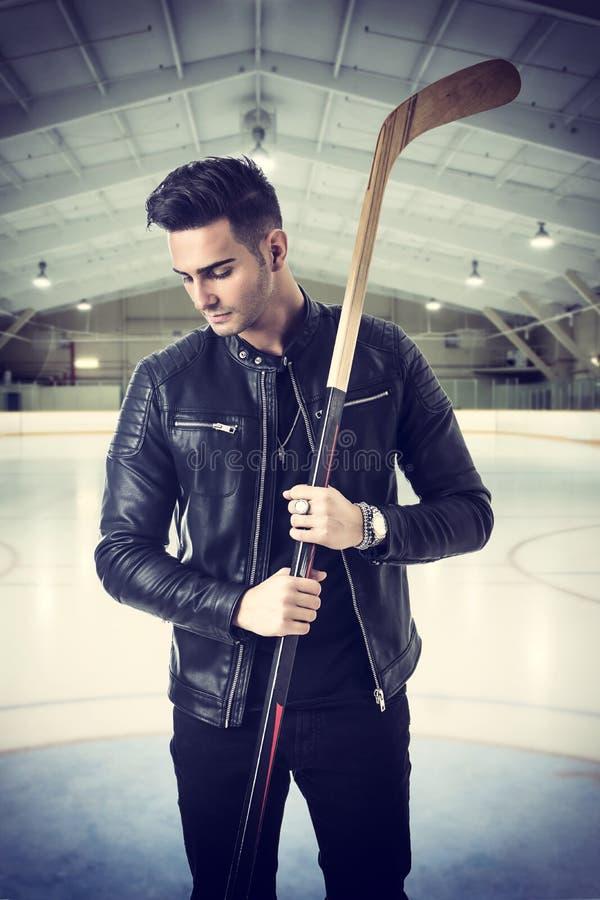 Красивый молодой человек с хоккейной клюшкой стоковая фотография rf