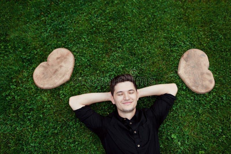 Красивый молодой человек усмехаясь и лежа на траве между 2 сердцами древесины стоковые фото