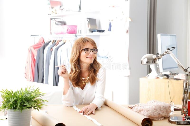 Красивый модельер работая в ее студии стоковые изображения