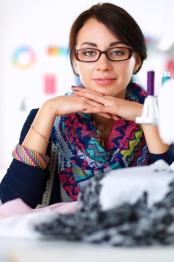 Красивый модельер сидя на столе в студии стоковые фото