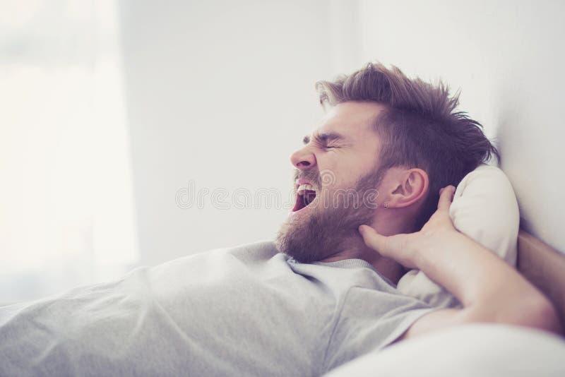 Красивый молодой американский мужской зевок спать в кровати дома стоковое фото rf