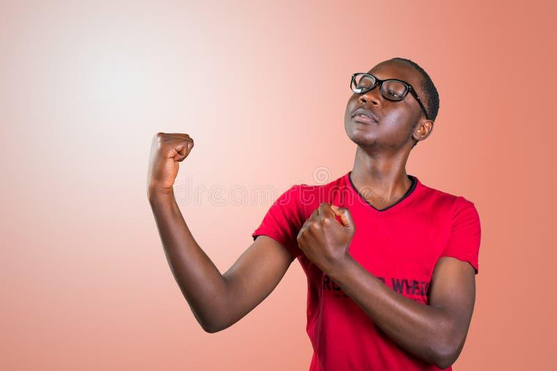 Красивый молодой Афро-американский человек, показывая его физические данные стоковое фото rf