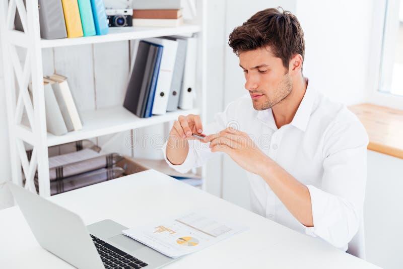 Красивый молодой бизнесмен принимая фото документов с smartphone стоковое фото