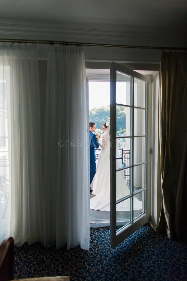 Красивый молодой жених и невеста стоя лицом к лицу на балконе в гостиничном номере стоковое фото
