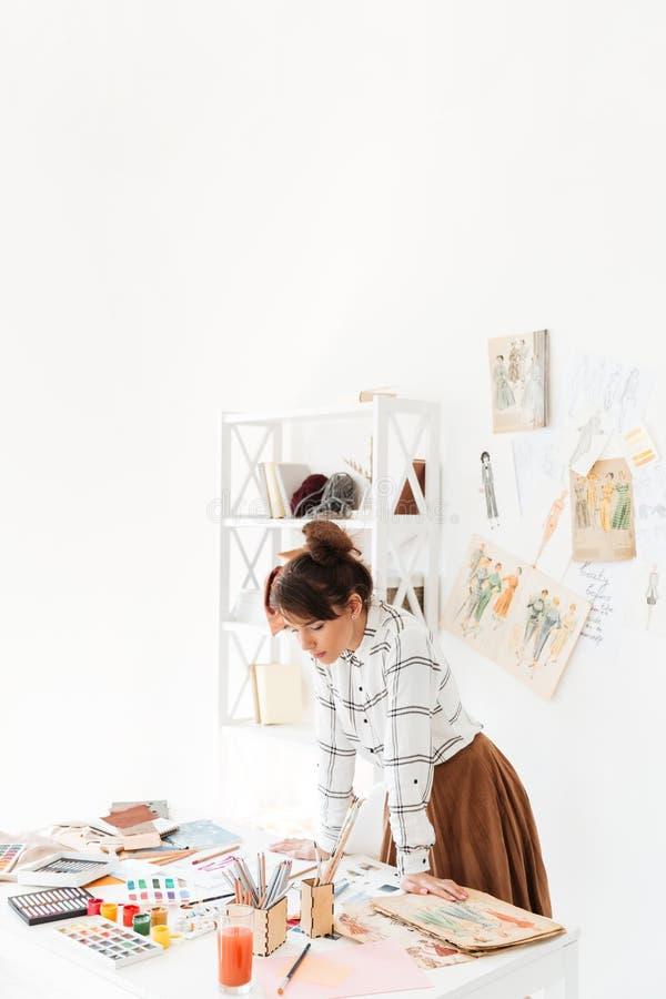 Красивый молодой женский модельер работая в студии стоковое изображение