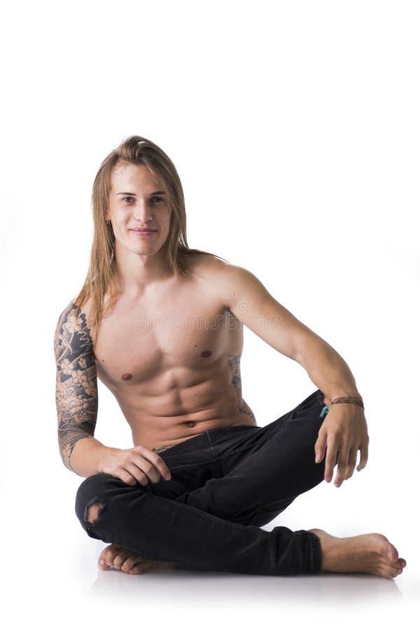 Красивый молодой длинный с волосами человек без рубашки, сидящ на поле стоковые фото