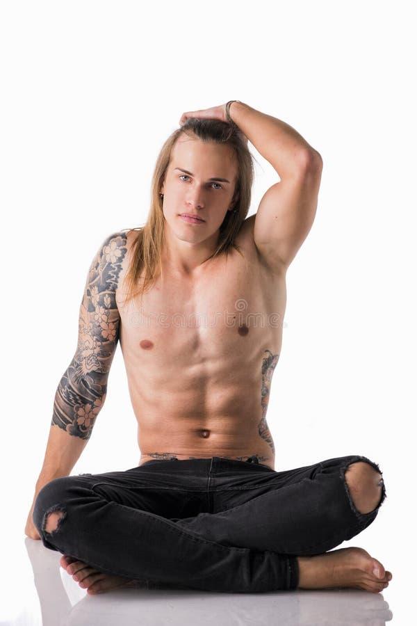 Красивый молодой длинный с волосами человек без рубашки, сидящ на поле стоковое фото rf