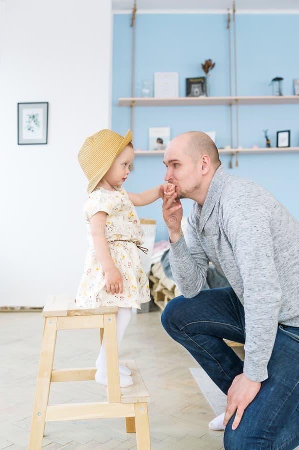 Красивый молодой отец целует руку его милой маленькой девочки стоковое изображение