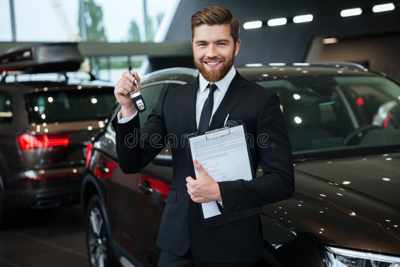 Красивый молодой продавец автомобилей стоя на дилерских полномочиях стоковое изображение rf