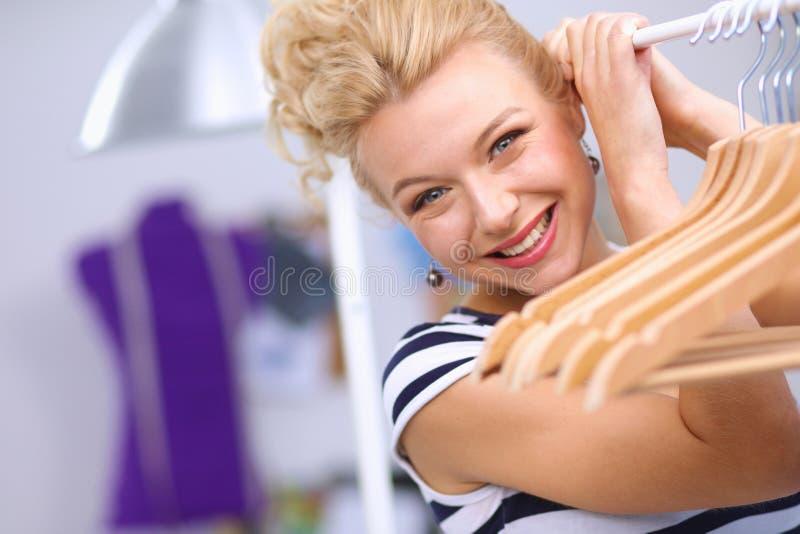 Красивый молодой стилизатор около шкафа с вешалками стоковые фото