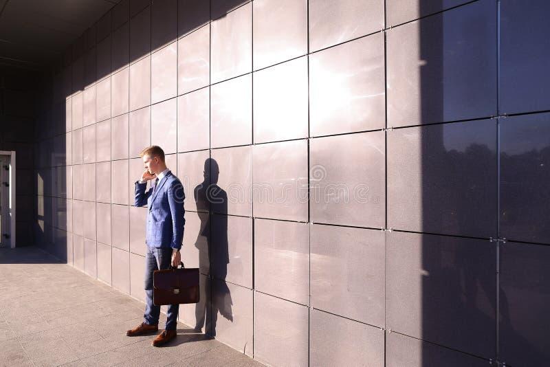 Красивый молодой человек, бизнесмен, студент говоря на телефоне и st стоковое изображение