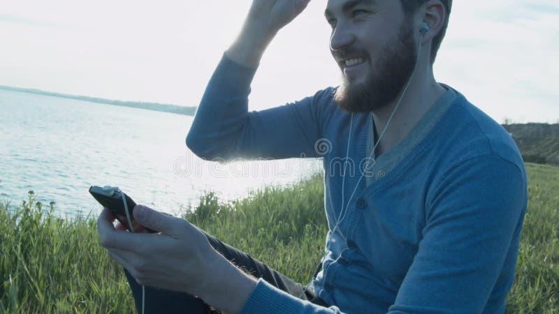 Красивый молодой человек в стеклах около моря на заходе солнца пишет sms на smartphone Счастливый стильный человек с наушниками видеоматериал