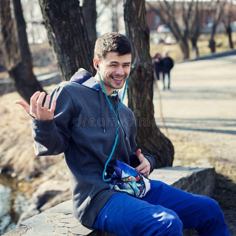 Красивый молодой человек играя гитару мнимую и слушая к музыке стоковое изображение rf