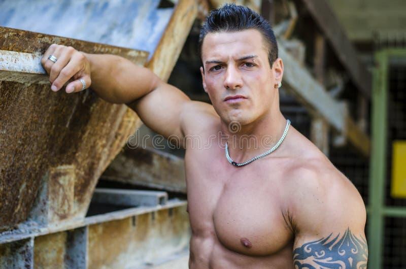 Красивый молодой человек мышцы с рукой на ржавой структуре металла стоковая фотография rf