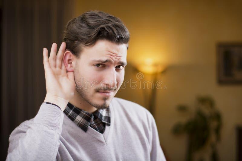 Красивый молодой человек не может услышать, кладущ руку вокруг его уха стоковые изображения rf