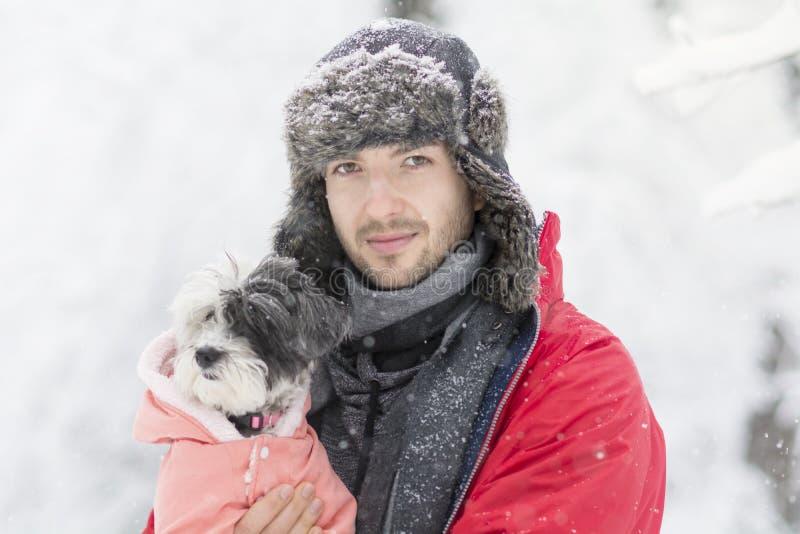 Красивый молодой человек обнимая его малую белую собаку в зиме snowing стоковое фото rf