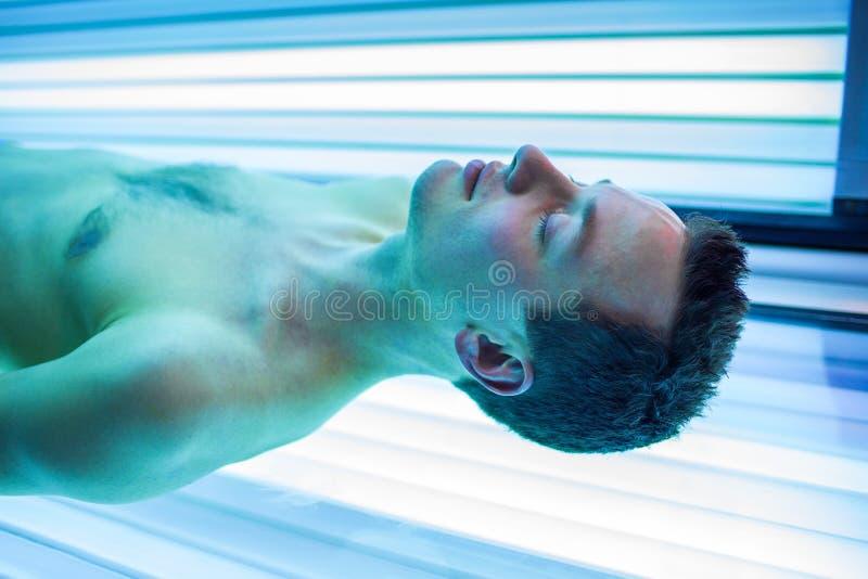 Красивый молодой человек ослабляя в самомоднейшем solarium стоковое изображение