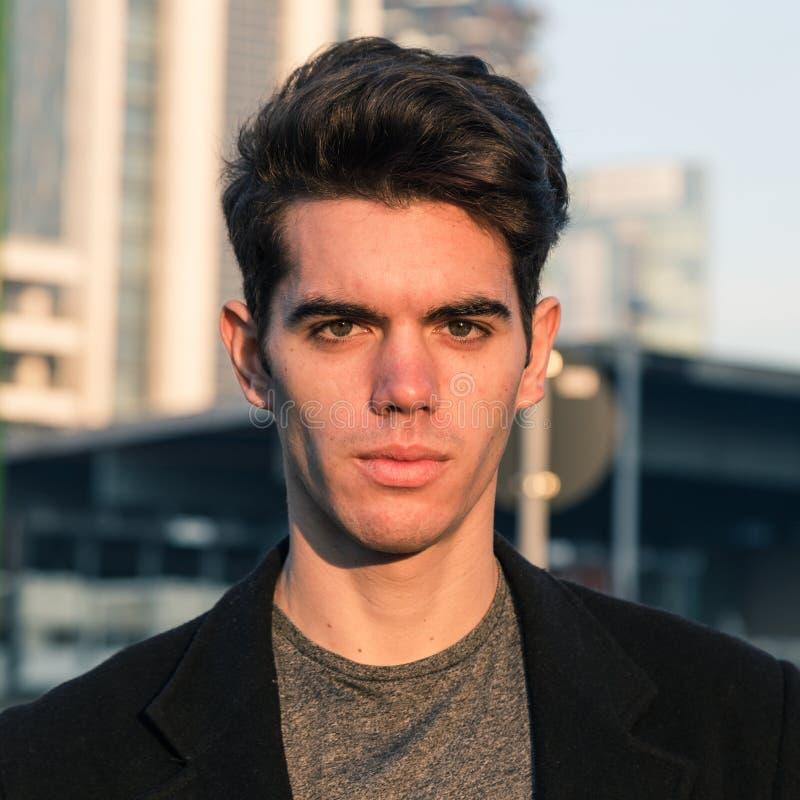 Красивый молодой человек представляя в городском контексте стоковое фото rf