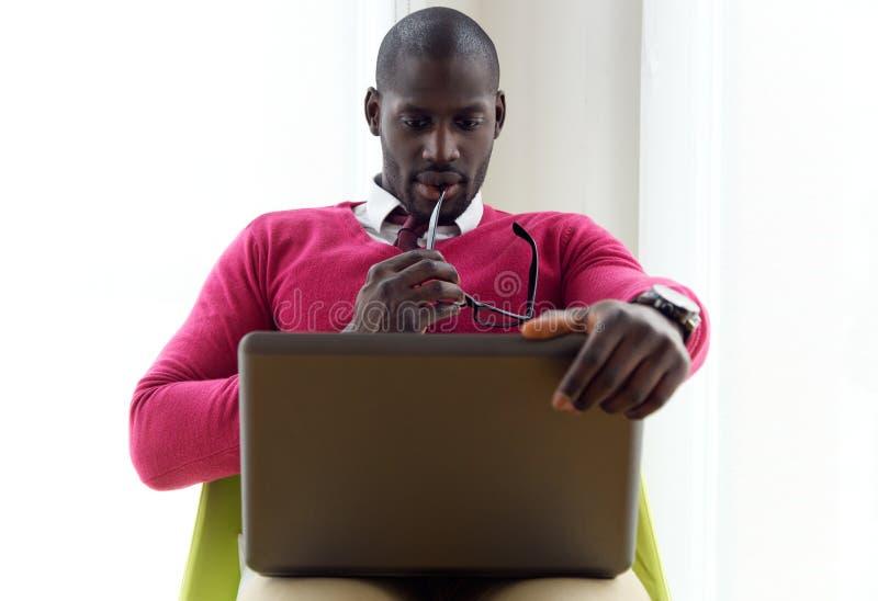 Красивый молодой человек работая с его компьтер-книжкой дома стоковые фотографии rf