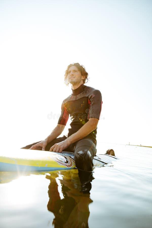 Красивый молодой человек серфера в swimwear сидя на доске прибоя стоковое изображение rf