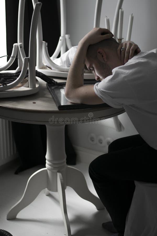 Красивый молодой человек сидит самостоятельно унылое в белой квартире, держит голову с руками и смотрит в зеркало на таблице стоковая фотография