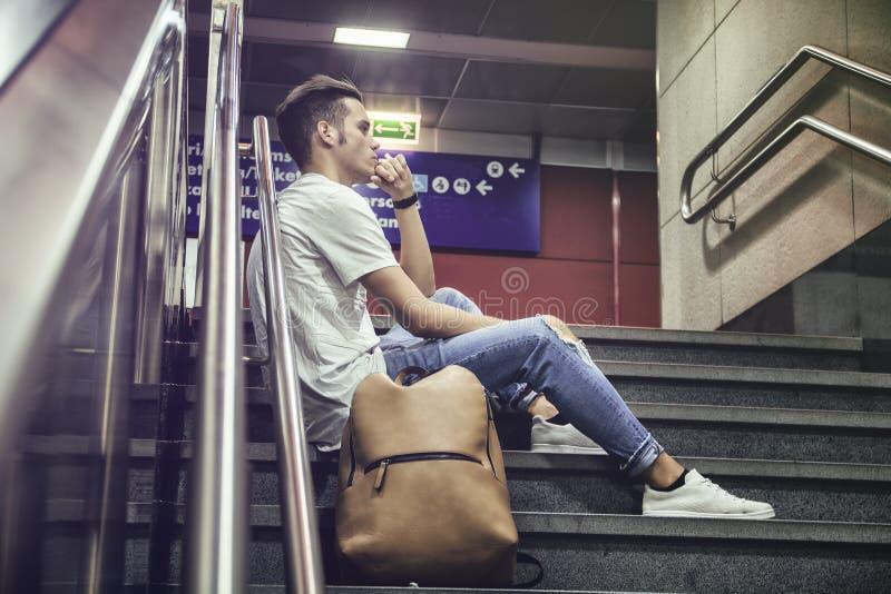 Красивый молодой человек сидя на лестницах стоковое фото