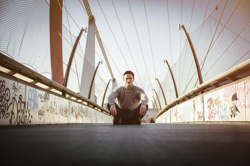 Красивый молодой человек сидя outdoors в городской среде стоковое изображение rf