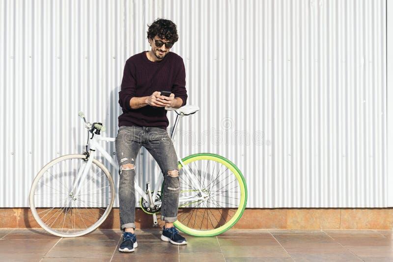 Красивый молодой человек с мобильным телефоном и фиксированная шестерня bicycle стоковые фотографии rf