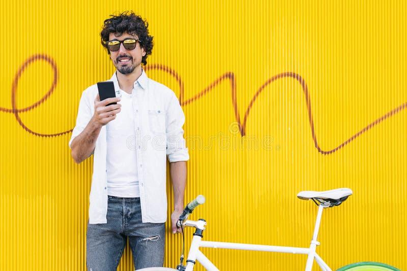 Красивый молодой человек с мобильным телефоном и фиксированная шестерня bicycle в t стоковое фото rf