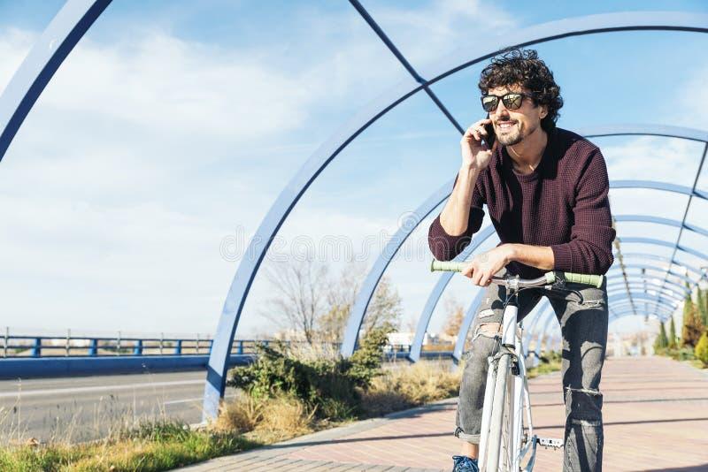 Красивый молодой человек с мобильным телефоном и фиксированная шестерня bicycle в t стоковые фото