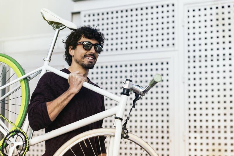 Красивый молодой человек с фиксированным велосипедом шестерни стоковое изображение